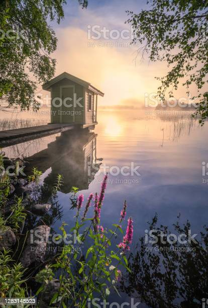 Photo of Beautiful morning landscape with little swim cottage, pier and foggy sunrise in lakeside Finland