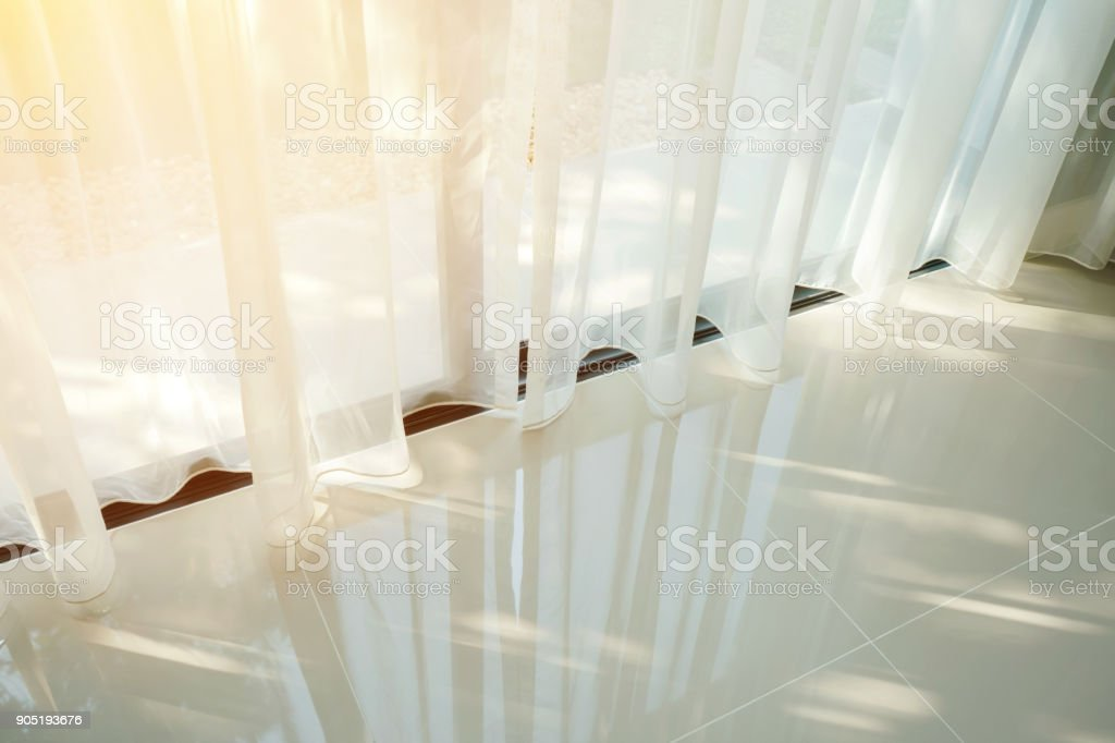 Beautiful morning light through sheer curtain in bedroom stock photo