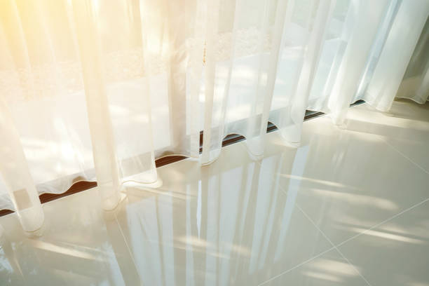 Beautiful morning light through sheer curtain in bedroom stock photo
