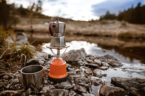 Making coffee by a small lake in nature