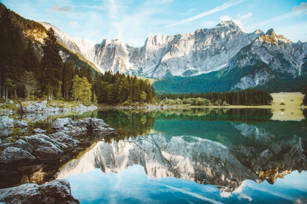schöne morgenszene mit alpengipfeln, die sich bei sonnenaufgang im ruhigen bergsee spiegeln - friaul julisch venetien stock-fotos und bilder