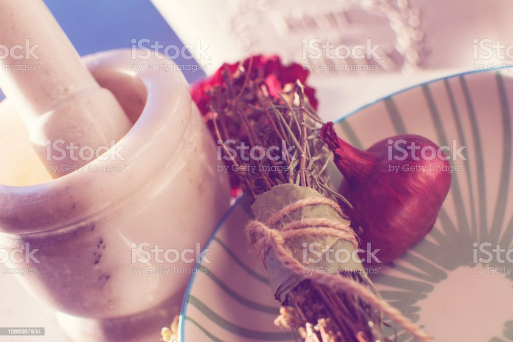 Beautiful Mortar and Pestle with herbs wrapped in string and red onion cooking closeup photography stock photo
