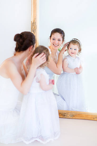 schöne mutter und niedlichen kleinkind tochter versuchen auf weißen kleider - hochzeitsspiele eltern stock-fotos und bilder
