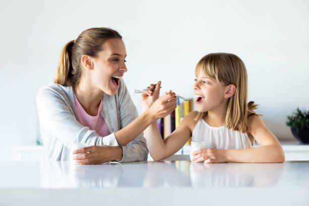 Schöne Mutter und Tochter füttern Joghurt zu Hause. – Foto