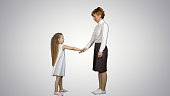 Beautiful mother and daughter giving high five and smiling each other on white background. Professional shot in 4K resolution. 095. You can use it e.g. in your commercial video, business, presentation, broadcast video.