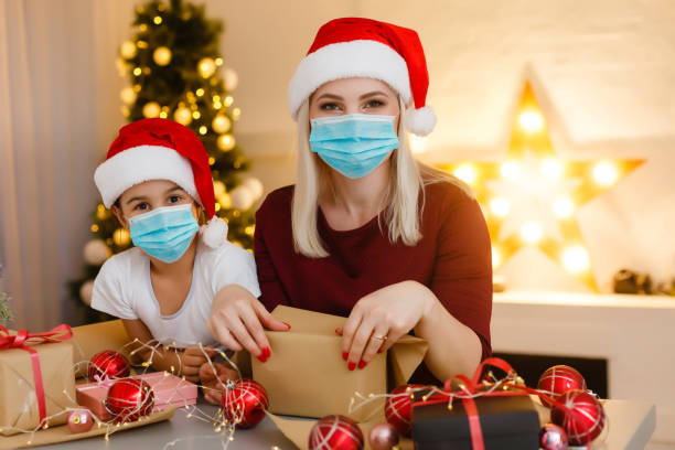 Beautiful mother and daughter in medical masks have fun at home near the Christmas tree in a white interior. Family happiness, holiday, joy, vacation, games with a woman. New Year's preparations. Cele stock photo