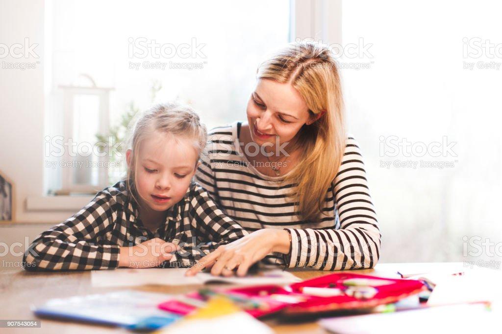 schöne Mutter und Tochter gemeinsam Schularbeiten zu Hause zu tun – Foto