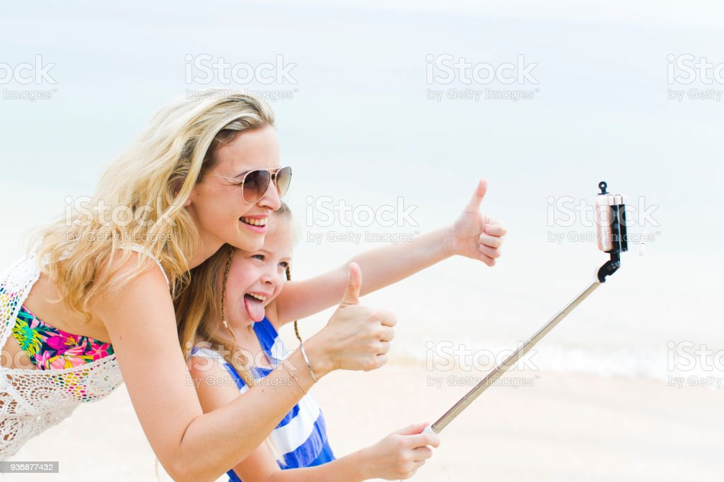 beautiful mother and her cute daughter doing a selfi with her phone on a beach in thailand stock photo