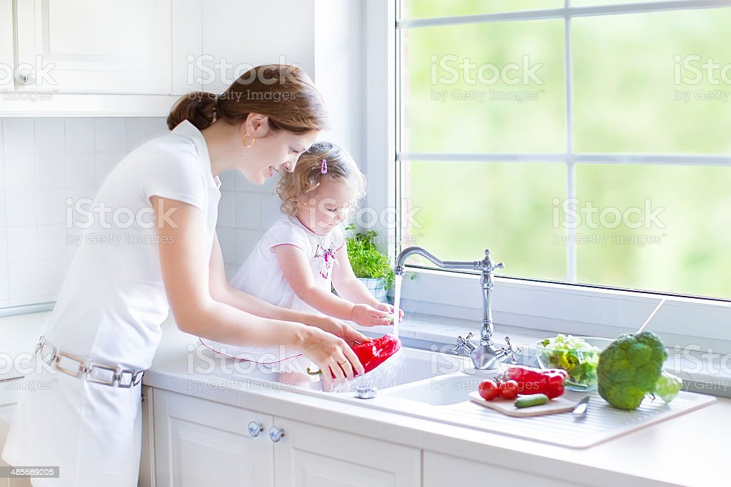 Beautiful mother and her daughter washing vegetables in kitchen sink stock photo
