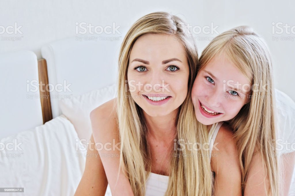 Schöne Mutter und ihre hübsche Tochter Teenager zu Hause lächelnd – Foto