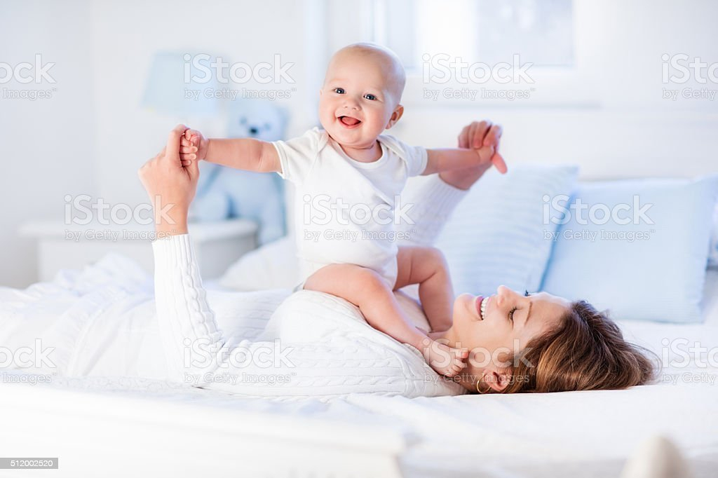 Beautiful mother and sweet baby on a white bed stock photo