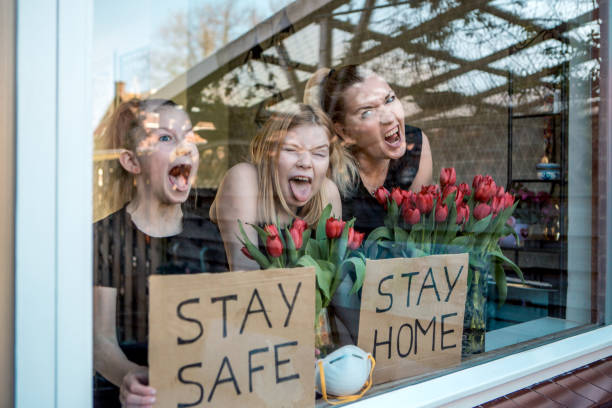 A beautiful mother and two young daughters at home during the lockdown A beautiful mother and two young daughters respecting the stay at home governmental directive during the corona lockdown due to the Covid-19 virus outbreak in Europe stay at home order stock pictures, royalty-free photos & images