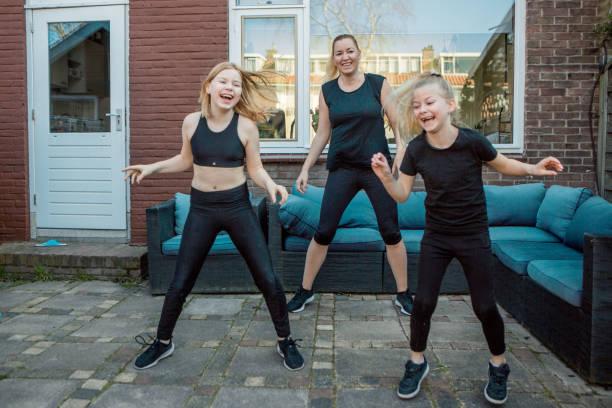 Eine schöne Mutter und kleine Töchter, die während der Sperrung zu Hause arbeiten – Foto