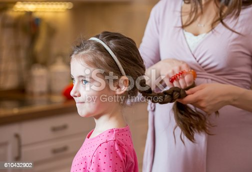625205382 istock photo Beautiful  mother braiding hair of her daughter 610432902