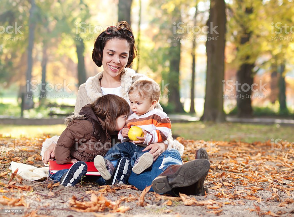 Beautiful mother embracing her little children in a autumn park royalty-free stock photo