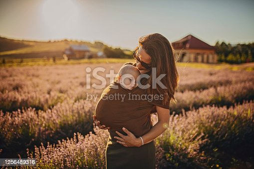 Happy young mother enjoying with her baby son in the lavander field on beautiful sunny summer day.