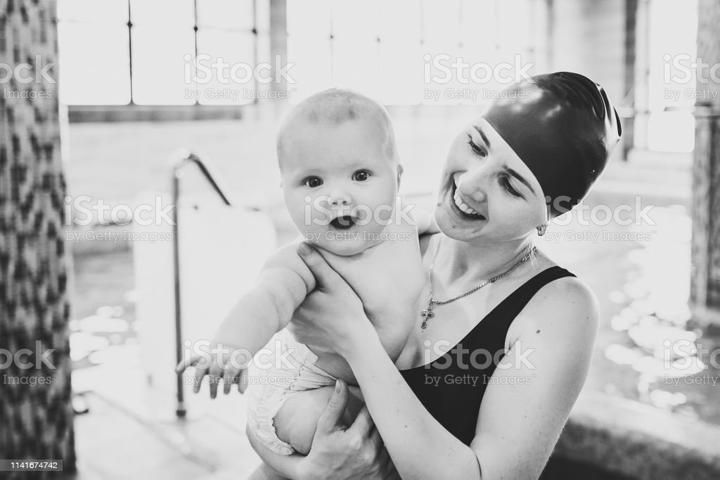 Beautiful mother holding a baby girl 6 months, a baby in her arms at...