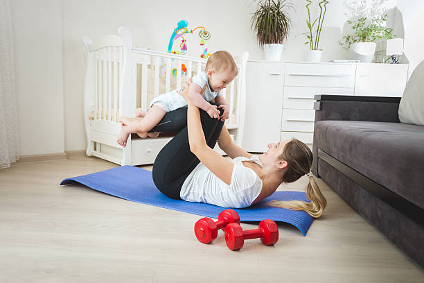 Beautiful mother holding baby and practicing yoga stock photo