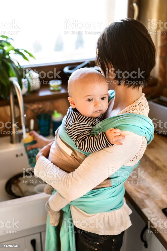 Beautiful mother in kitchen washing dishes, her son in sling stock photo