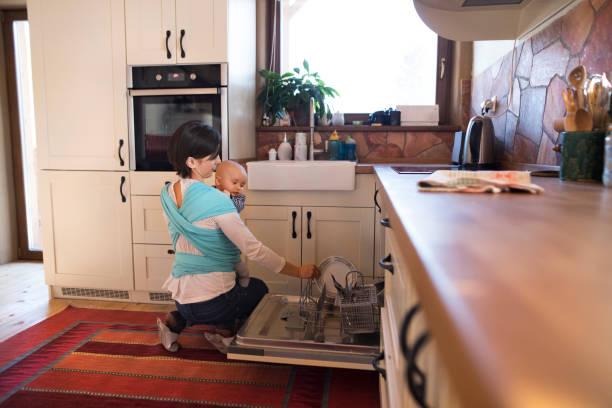 schöne mutter in küche, geschirrspülen, ihren sohn in schlinge - backofenfenster reinigen stock-fotos und bilder