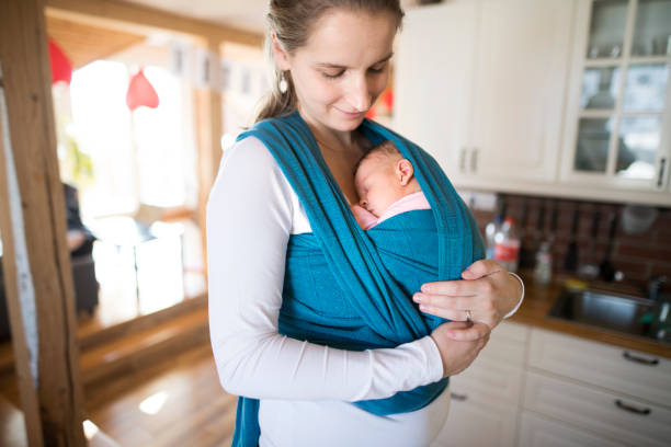 Beautiful mother in kitchen with her daughter in sling stock photo