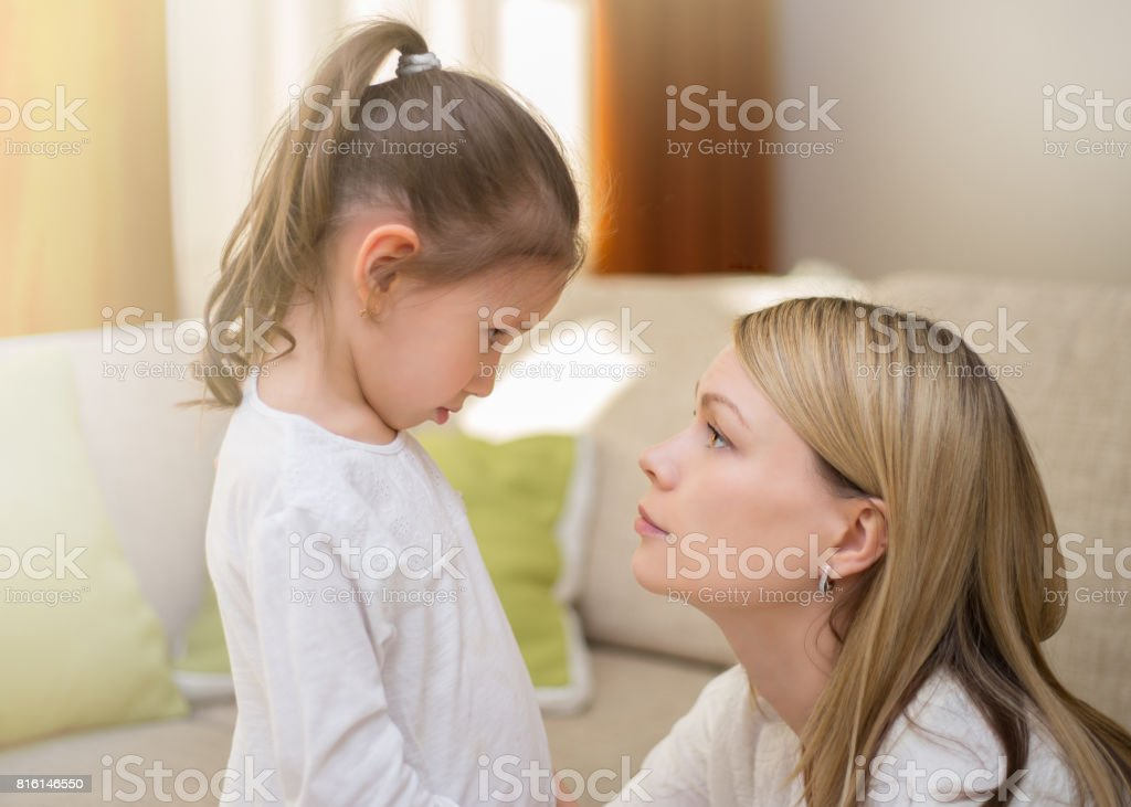 Beautiful mother is comforting her sad little daughter at home. stock photo