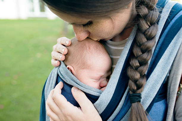 beautiful mother kissing her son in sling, green nature - xaile imagens e fotografias de stock