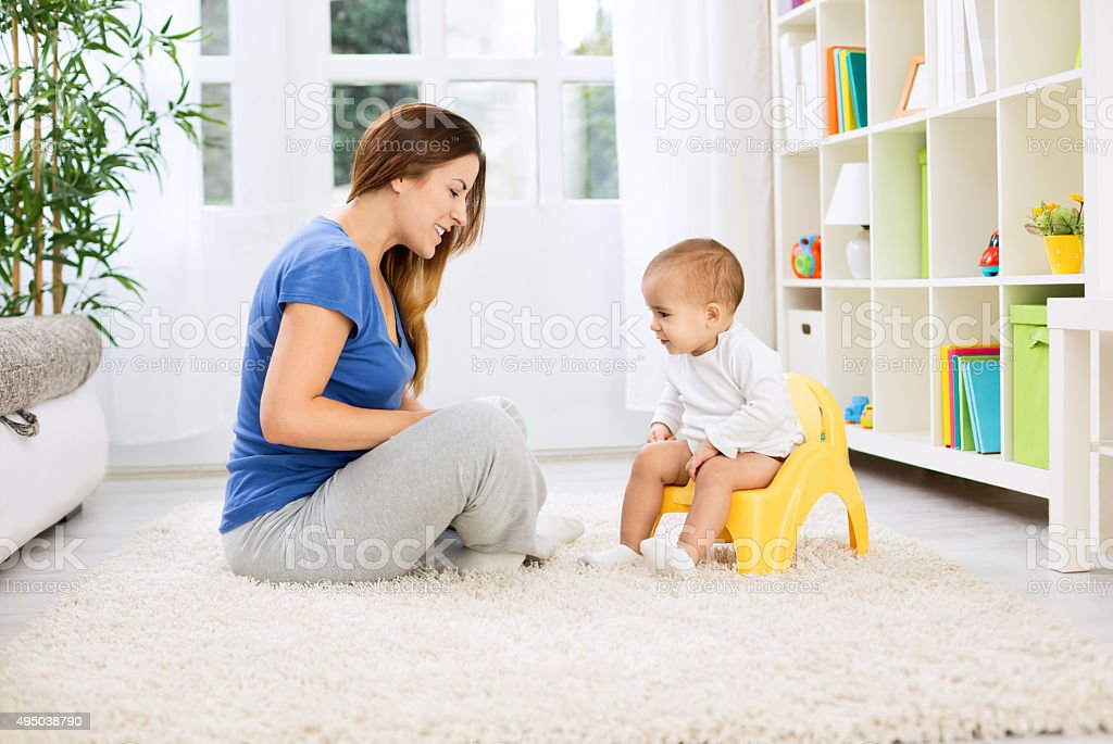 Beautiful mother learning little child how to sitting on potty stock photo