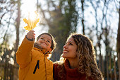 istock Beautiful mother looking at a leaf her son is holding on a sunny autumn day at the park 1194910110
