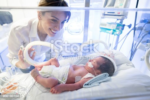 Beautiful mother looking at her premature baby in the incubator with oxygen at the neonatal intensive care unit