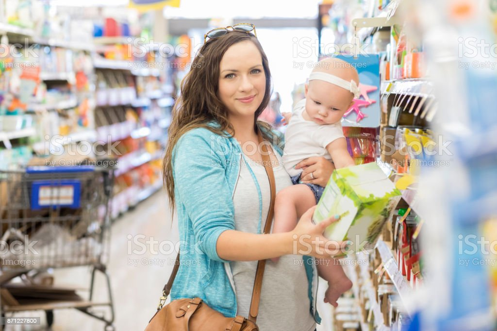 Beautiful mother reads product label while shopping in grocery store stock photo