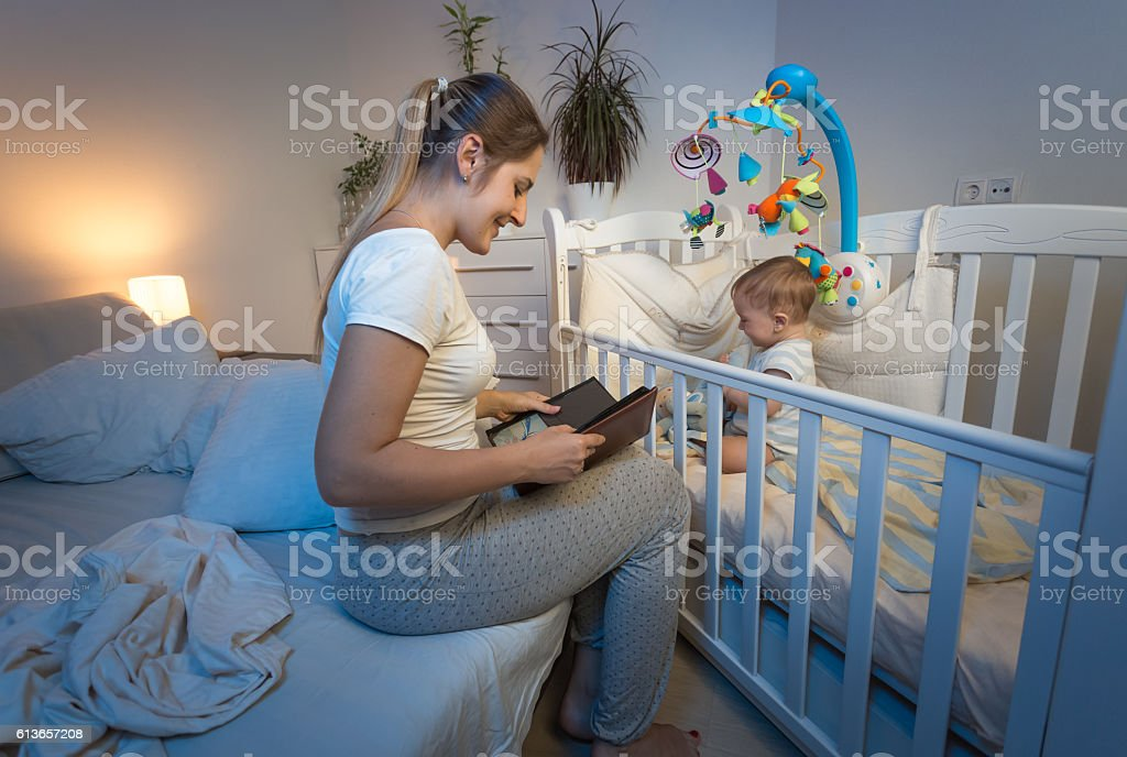 Beautiful mother sitting at baby's crib and reading a book stock photo