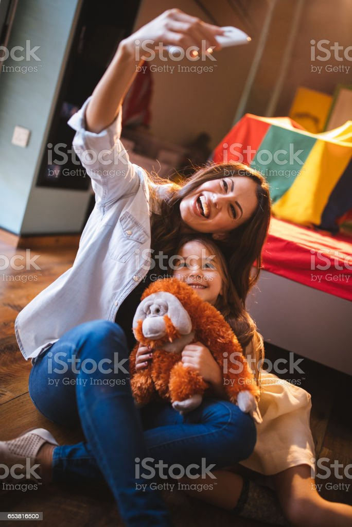 Beautiful mother taking smiling selfie with daughter and her toy stock photo