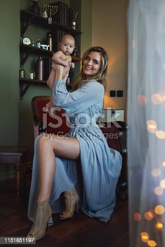 Young beautiful mother wearing luxury grey dress sitting in the armchair and holding her baby on hands