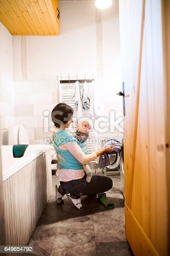 istock Beautiful mother with baby in sling in bathroom washing clothes 649654792