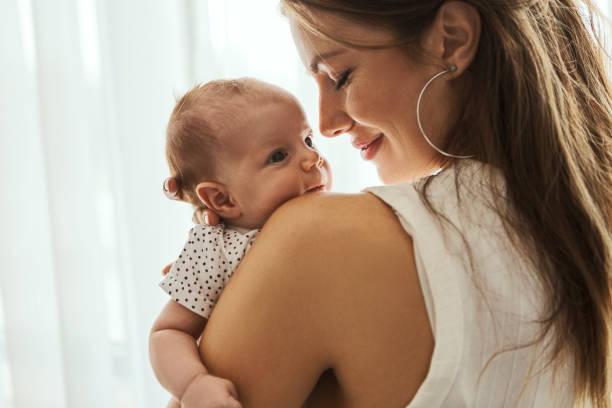 Schöne Mutter mit ihrem Baby auf einer Schulter – Foto