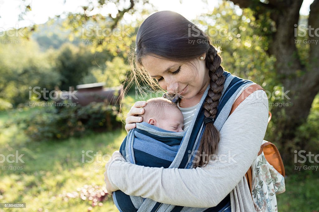 Beautiful mother with her son in sling, green nature stock photo