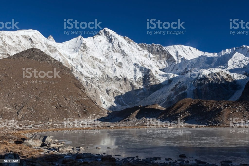 Beautiful mountain Cho Oyu and gray moraine lake covered stock photo