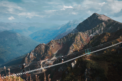 Beautiful mountain landscape with blue coudy sky. Suspension extreme bridge at Rosa Peak top