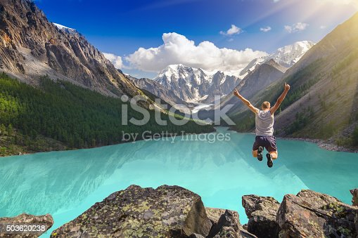 Beautiful mountain landscape with lake and jumping man. Extreme sports concept.