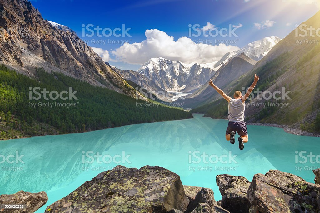 Beautiful mountain landscape with lake and jumping man stock photo