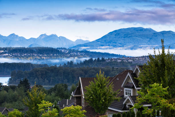 Beautiful mountain river scene at sunrise, BC, Canada Residential area at Surrey near Fraser river in autumn in a early morning, Coquitlam cityscape in the background. british columbia stock pictures, royalty-free photos & images