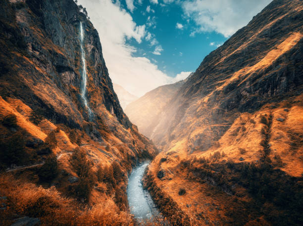 Beautiful mountains covered orange grass in autumn. Colorful landscape with mountain valley, river, waterfall, meadows and forest, sky with clouds in fall at sunset. Travel in Himalayas. Nature stock photo
