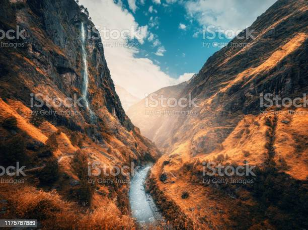 Photo of Beautiful mountains covered orange grass in autumn. Colorful landscape with mountain valley, river, waterfall, meadows and forest, sky with clouds in fall at sunset. Travel in Himalayas. Nature