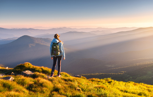 Beautiful mountains in fog and standing young woman with backpack on the peak at sunset in summer. Landscape with sporty girl, green grass, forest, hills , blue sky with sunbeams. Travel and tourism