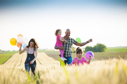 Beautiful multi ethnic family running through wheat field