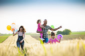 Beautiful multi ethnic family running through wheat field, they holding balloons