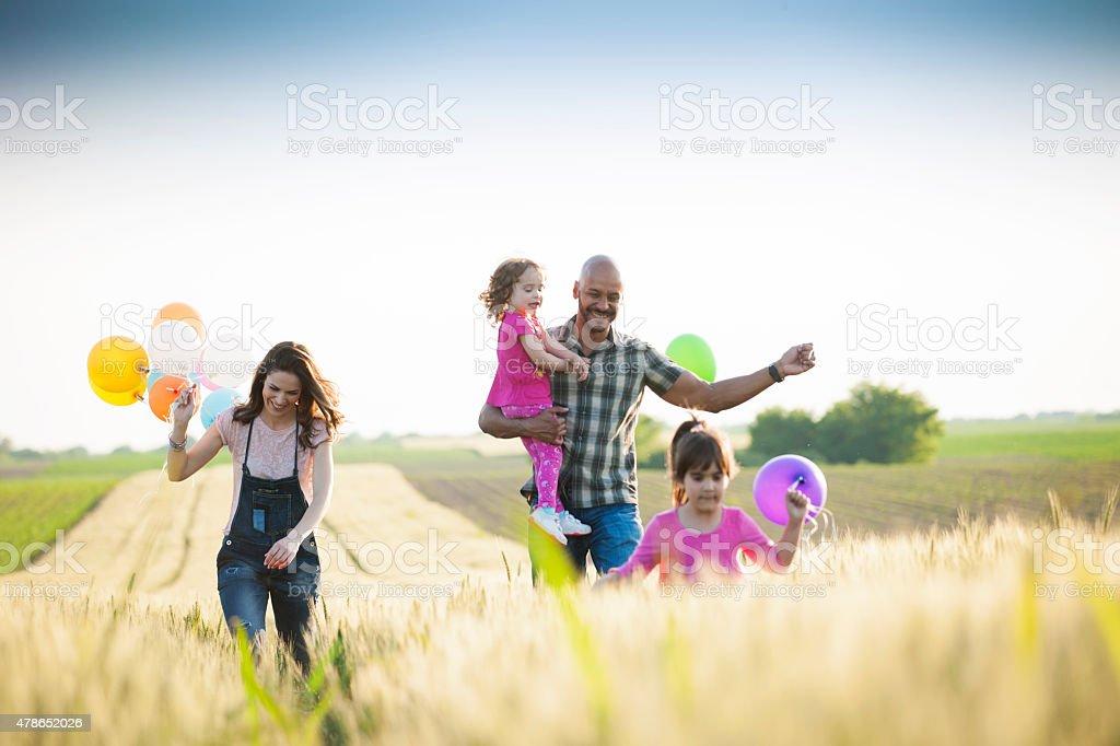 Beautiful multi ethnic family running through wheat field stock photo