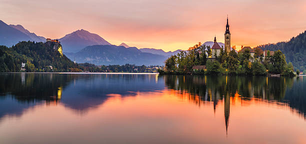 beautiful, multicolored sunrise over an alpine lake bled in slovenia - eslovênia - fotografias e filmes do acervo