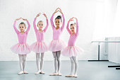 istock beautiful multiethnic kids in pink tutu skirts practicing ballet together 1011870580